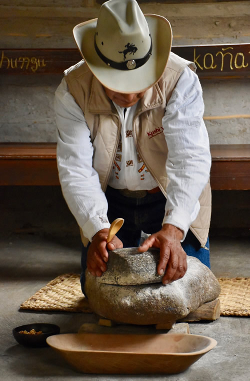 "Alfonso grinding corn on the stone ""mill."""