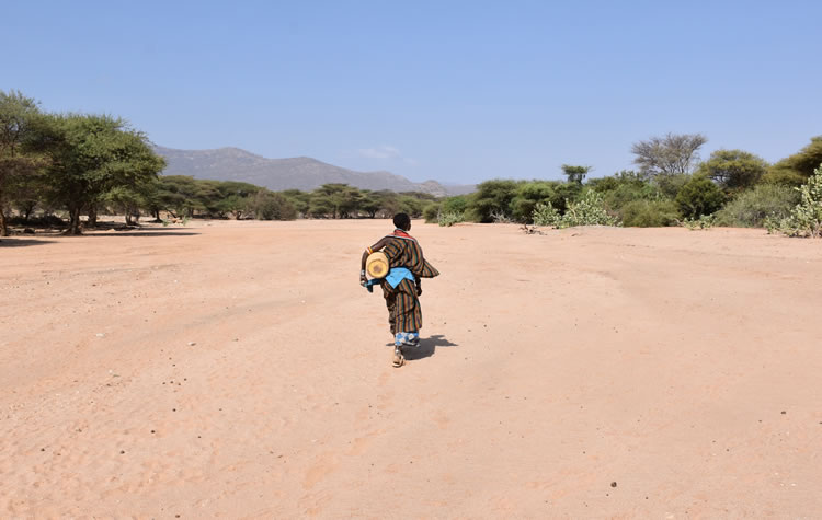 Woman with jerrycan on her way to a water well