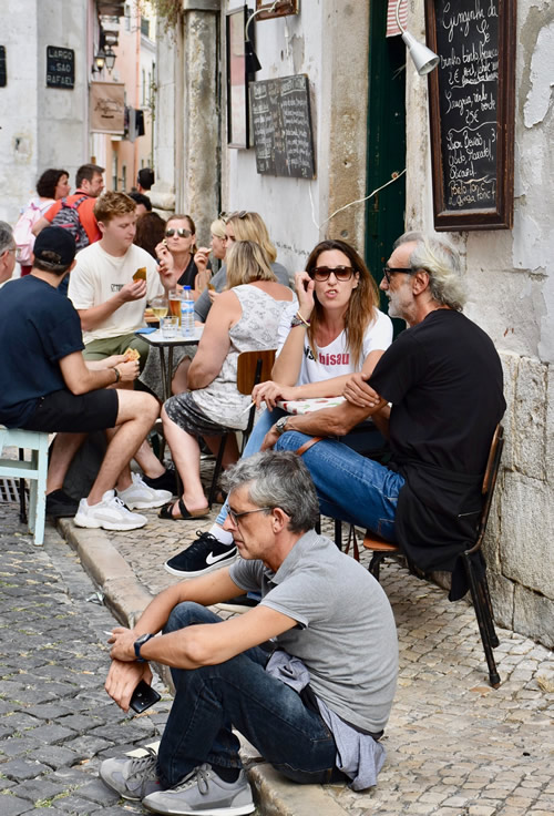 Eating and drinking on the narrow Alfama sidewalks, a historic district of Lisbon