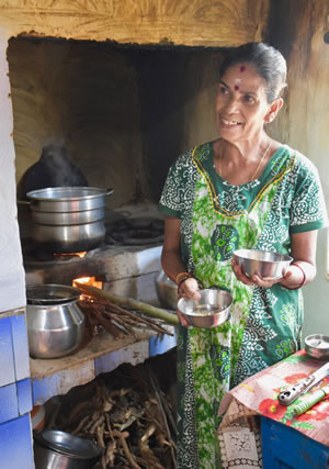 Hostess in her kitchen baking dosas