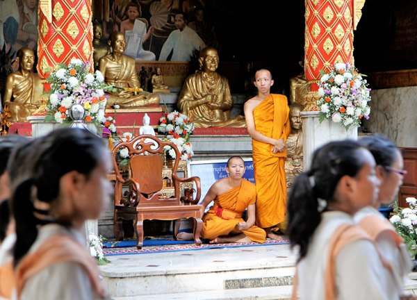 Monks watch a processional during the annual Chiang Mai University Welcoming Celebration