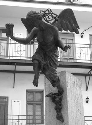 A statue in Prague of an angel holding a beer