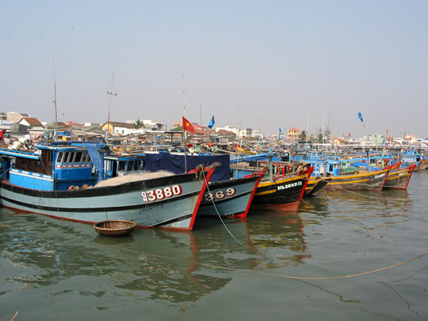 Wooden fishing boats in Vietnamese village harbor.