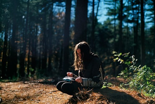 Teen reading in the woods