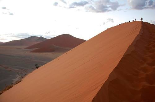 Group adventure travel climbing a sand dune in Namibia