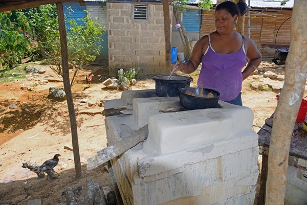A woman cooking lunch outdoors, over an open fire hearth
