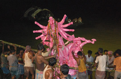 A group men lower clay idol of goddess Durga into river