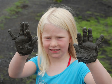 Child showing mud from the flooded grass lands