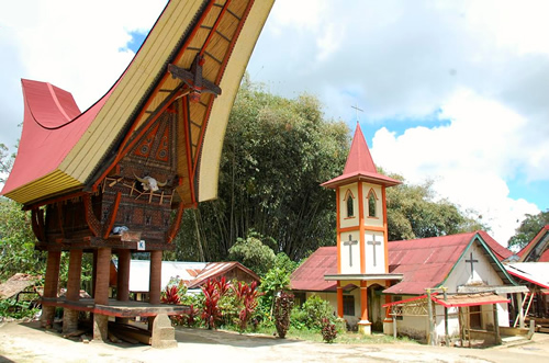 Tongkonan and a Christian church in Sulawesi, Indonesia