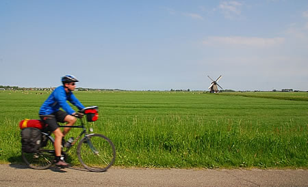 Andrew cycling with a windmill in the background