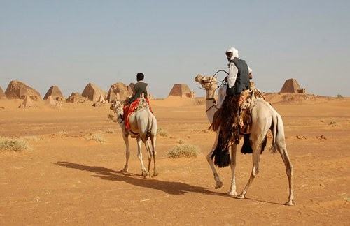 Men on camels at pyramids