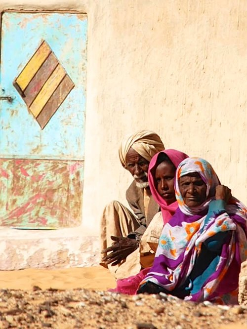 A curious family in front of their house with typical Nubian door