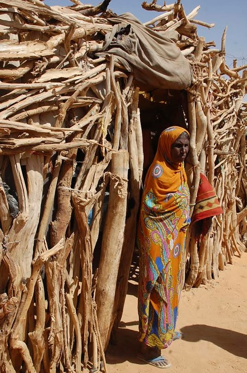 Nomad woman in front of her home made from acacia branches