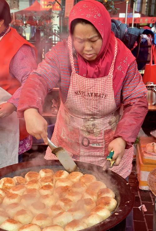 Woman busy cooking at the Friday Muslim Market