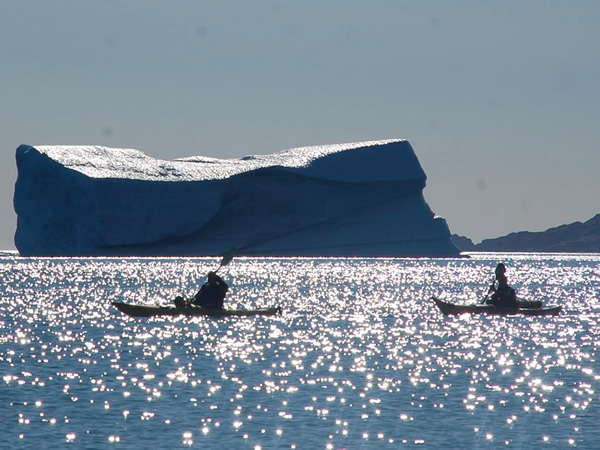 In paddling boats near an iceberg in the Artic