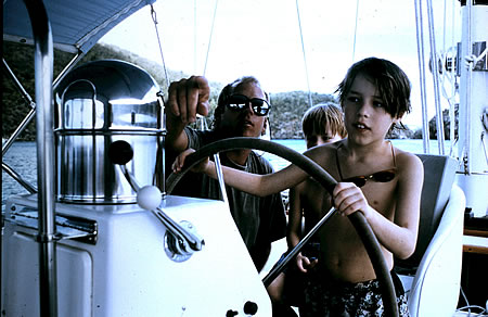 Son guiding a yacht with family