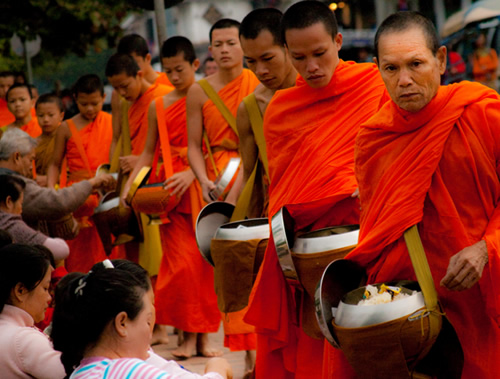 Monks accepting alms of sticky rice during a ceremony