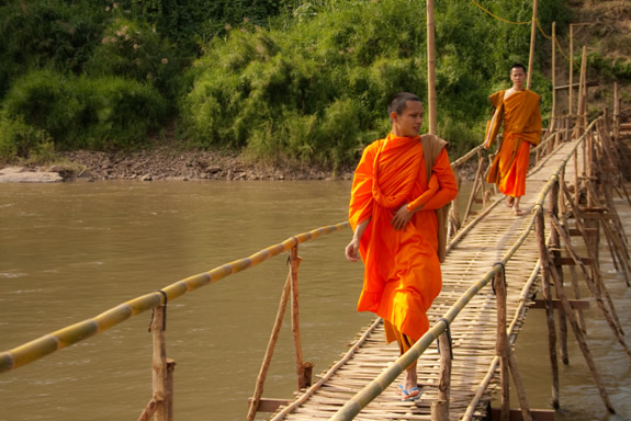 Monks crossing a bridge in Laos
