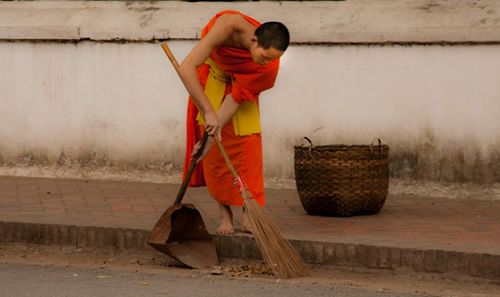 Monk sweeping the street