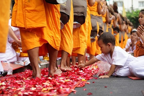 A boy reaching for rose petals during a Buddhist festival in Bangkok