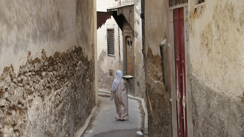 Woman takes bread to public oven in the medina of Fez