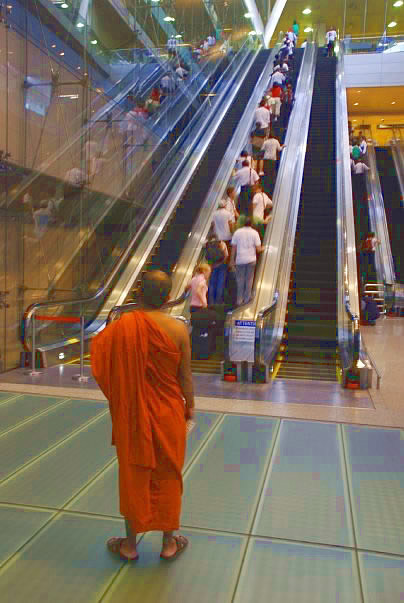 Monk going up escalator in Singapore