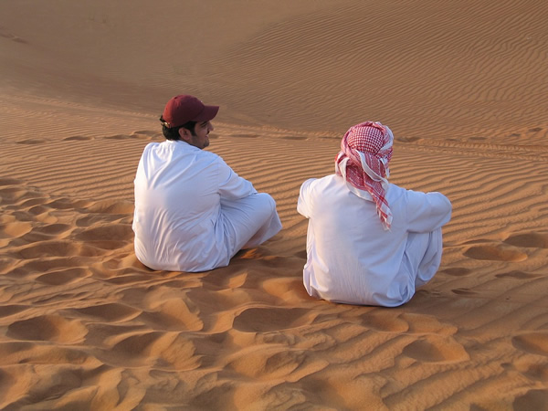Friends sitting in sand in the Middle East
