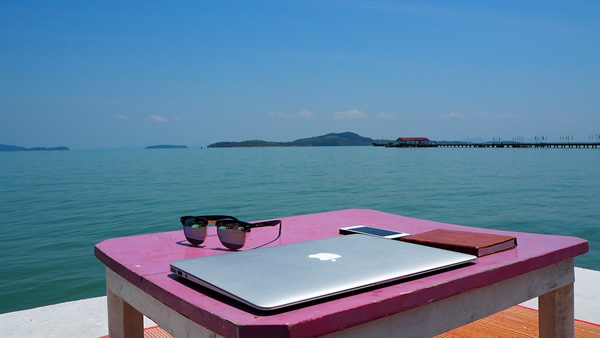 Thailand digital nomad freelancing with laptop overlooking ocean