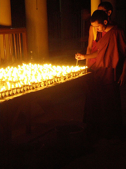 Lighting butter lamps at the Dalai Lama's temple