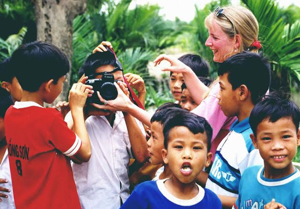 Beth showing children from an orphanage in Vietnam how to take photos