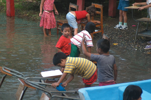Children washing desks in the river