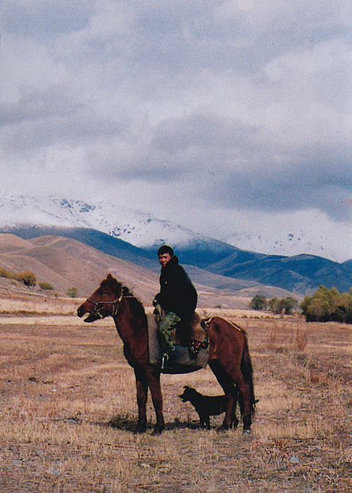 Kyrgyzstan man on horse with dog