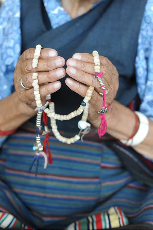 Host grandma with prayer beads in Dharamsala