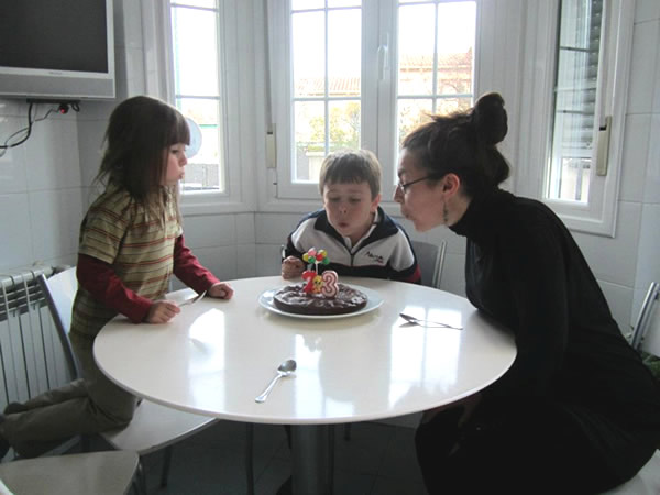 Blowing out birthday candles in Madrid home with children