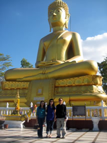 In front of giant golden Buddha in Thailand
