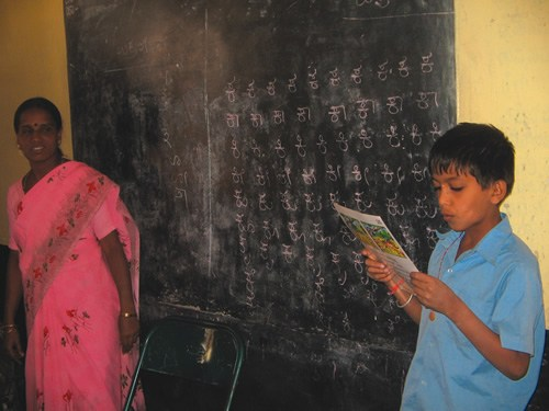 Child in India Reading as Teacher Looks On